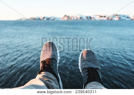 Brave Traveler Sitting On Cliff And Looks On Legs And Shoes. Pov View On Feet On Background Of Ocean