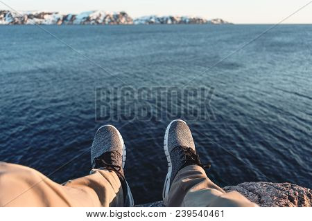 Brave Man Sitting On Cliff In Front Of Breakage Above Sea And Snow Mountains. Pov View Of Legs And S