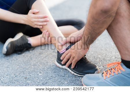 Ankle Sprained. Young Woman Suffering From An Ankle Injury While Exercising And Running And She Gett