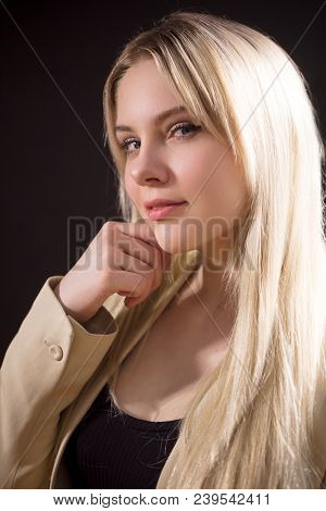 Profile View Of Beautiful Young Woman Looking At Camera With Catty Eyes , On Dark Background