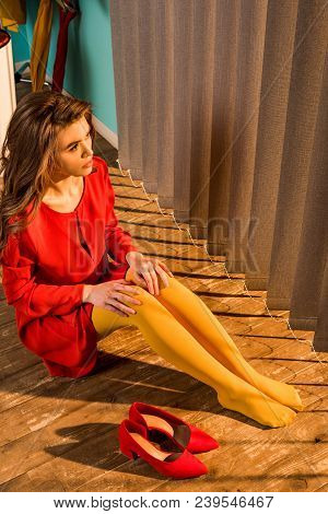 High Angle View Of Retro Styled Woman In Red Dress Sitting On Floor And Looking At Jalousie At Home