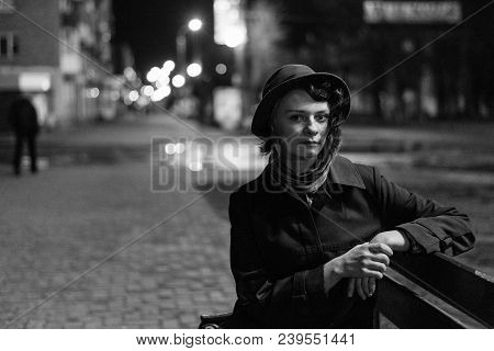 Cute Girl In A Hat Sits On A Bench On The Street At Night, Photographed On Film, Photo Film Grain, B