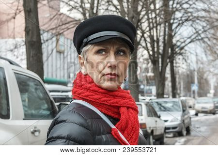 Pretty And Serious Middle-aged Lady In A Red Scarf, Cap, Earrings And Black Jacket Against The Backg