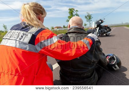 A german paramedic helps an injured motorcyclist. Rettungsdienst is the german word for ambulance service. poster