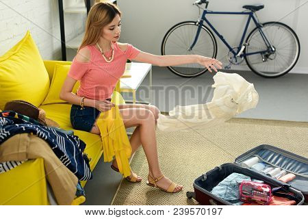 Girl Throwing Clothes Into Suitcase For Voyage