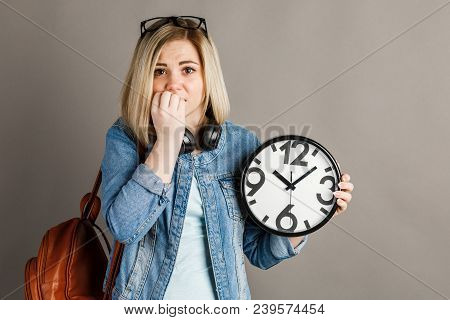 Girl Student With A Big Clock In Hands. On A Gray Background.