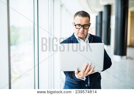 Always Ready To Help You. Cheerful Mature Man In Formalwear Adjusting His Eyeglasses And Holding Lap