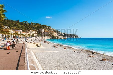 Nice, France - October 13, 2009: Bright Turquoise Sea, Blue Sky And People Relaxing On Beach That St