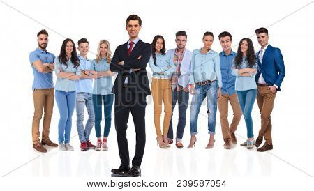 confident group leader standing on white background with hands folded while his casual team is behind him, full body picture