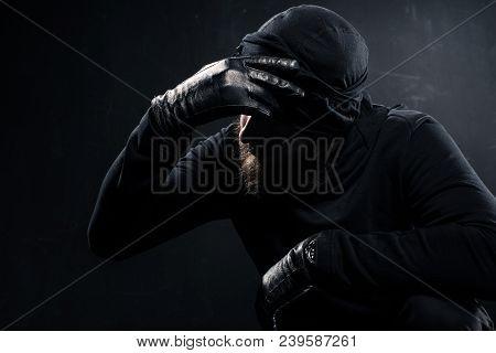 Burglar In Balaclava Leaning His Head On Hand