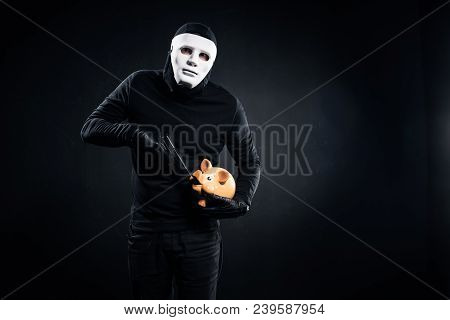 Burglar In Mask Holding Gun And Piggy Bank