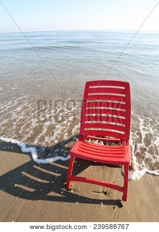 Red Chair Is Bathed By The Waves Of The Blue Sea