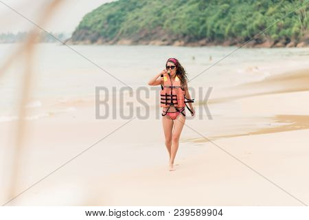 A Girl In A Life Jacket And Glasses Is Running Along A Deserted Beach. A Beautiful Curly Girl With A