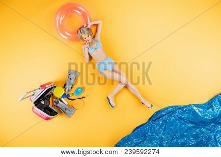Top View Of Beautiful Girl In Swimsuit And Flip Flops Lying On Inflatable Ring On Yellow