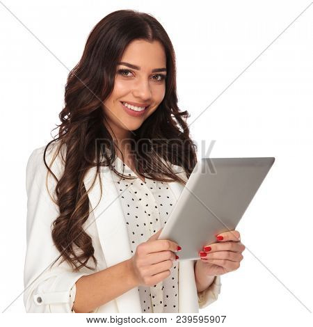 portrait of beautiful busineswoman holding tablet with both hands and smiling while standing on white background