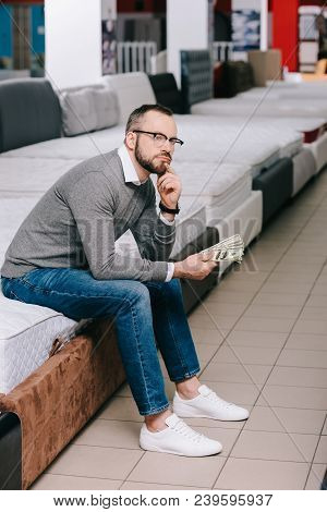Side View Of Pensive Male Shopper With Dollar Banknotes Sitting On Mattress In Furniture Store