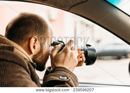 Private detective or reporter or paparazzi sitting in car and taking photo with professional camera, toned poster
