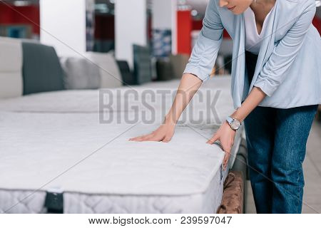 Partial View Of Woman Touching Orthopedic Mattress In Furniture Shop