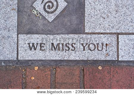 The Words We Miss You On A Motivational Brick Sidewalk Made Of Concrete And Mortar.