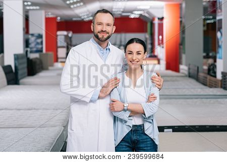 Portrait Of Smiling Shop Assistant And Female Shopper In Furniture Store With Arranged Mattresses