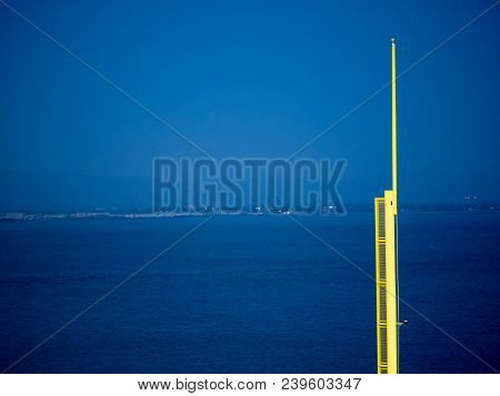 A Baseball Foul Pole Overlooking A Body Of Water At Night