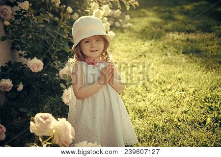 Girl In Hat With Praying Hands In Summer Garden. Child Standing At Blossoming Rose Flowers On Green