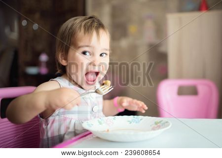 Little Baby Girl Having Her Meal By Herself