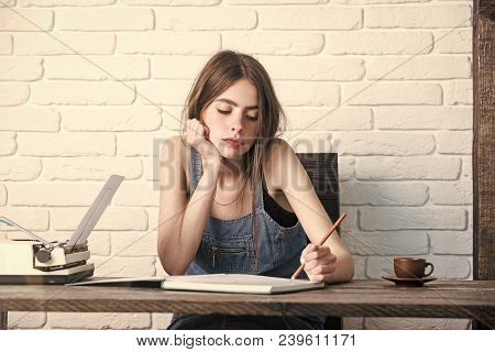 Teenager Student In Jean Pinafore On White Brick Wall. Girl Writing With Pencil In Notebook. Young W