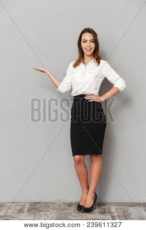 Full length portrait of a confident young business woman presenting copy space over gray background