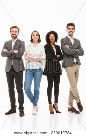 Full length portrait of a group of happy multiracial business people standing with arms folded isolated over white background