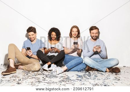 Group of happy multiracial people sitting on a floor with confetti and using mobile phones isolated over white background