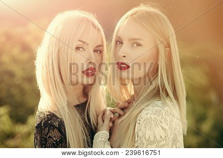 Two Women With Red Lips And Long Blond Hair. Contrasts And Opposites Concept. Sisters Twins Posing O