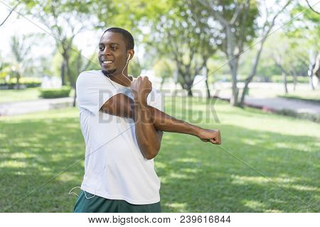 Smiling Sporty Black Man Listening To Music And Doing Morning Exercises In Park. Young Afro American