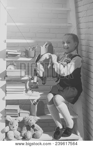 Kid In Study Room On Light Brick Background. Schoolgirl With Cheerful Face Puts Blue Book Into Schoo