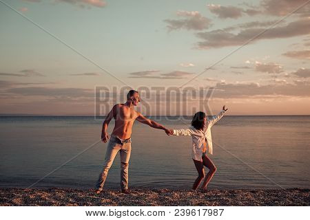 Man And Woman Hold Hands, Couple Happy On Vacation. Couple In Love Dancing, Having Fun, Sea And Skyl