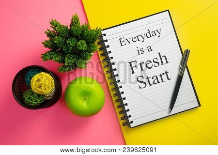 Everyday Is A Fresh Start. Inspirational Quote On Notebook With Pen, Green Apple And Potted Plant.