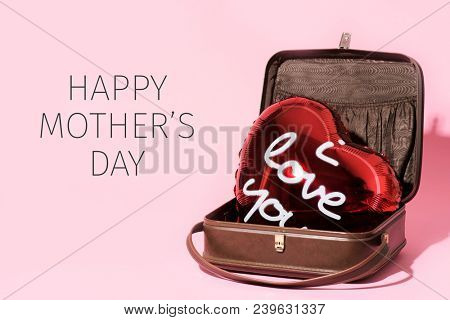 a red heart-shaped balloon, with the text I love you written in it, in an old suitcase and the text happy mothers day on a pink background
