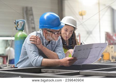Metal industry manager and engineer meeting in factory
