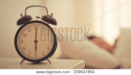 Alarm Clock Counting To Six O Clock With Woman Still Sleeping In Bed