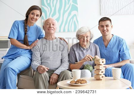 Senior man and woman with young caregivers indoors