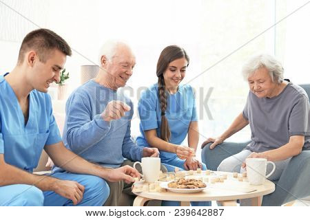 Senior people playing bingo with their caregivers indoors
