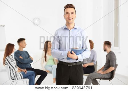 Male psychologist at group psychotherapy session indoors