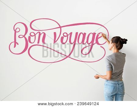 Artist woman writing Bon Voyage on the wall