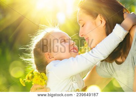 Happy Mother and little Daughter outdoor portrait. Mom and her child enjoying nature together in green park, kissing and hugging, happiness, love. Beauty family. Mother's Day concept
