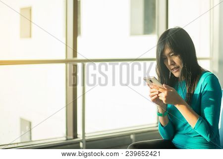 Asian Woman Passenger Holding Mobile Phone And Checking Flight Or Online Check In And Travel Planner