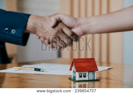Estate Agent Shaking Hands With His Customer After Contract Signature, Contract Document And House M