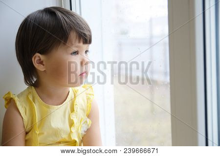 Little Girl Looking Out The Window Longing For Some Sunshine. Curiosity Childness. Child Sitting Hom