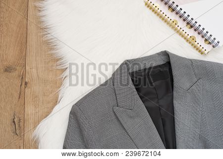 Elegant Women Jacket. Checkered A Gray Jacket On A Wooden Background. Concept Of Fashion And Design,