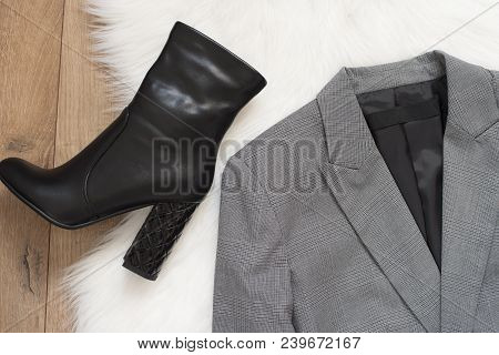 Elegant Women Jacket And Black High Heel Boots. Checkered A Gray Jacket On A Wooden Background. Conc