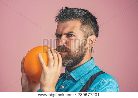 Concept For Happy Birthday, Celebration - Happy Father Is Blowing Orange Balloon. Handsome Bearded M